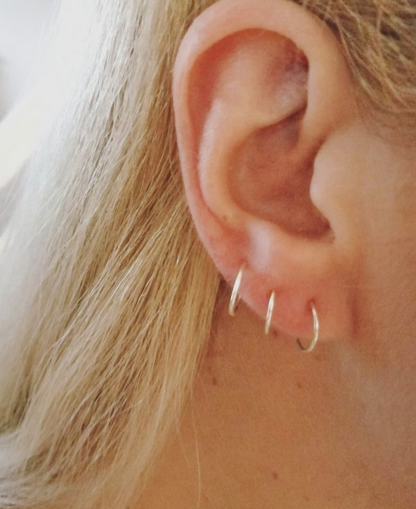 ear lobe piercings upper middle and standard position with silver hoops small sized